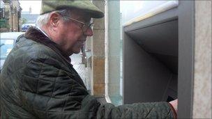John Shepherd-Barron using cash dispenser at Barclays bank in Enfield, north London