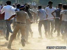 An Indian policeman runs towards a crowd with a lathi stick outside the Vidarbha Cricket Association (VCA) Stadium in Nagpur on March 8 2011