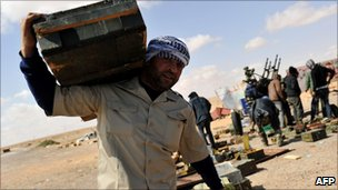 A rebel carries a box of ammunition near Ras Lanuf