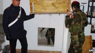 Italian policemen show the entrance to the bunker where a suspect was found, 8 March