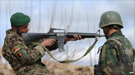 An Afghanistan National Army (ANA) soldier checks a weapon in Helmand Province on 2 March 2011