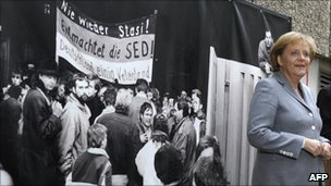 Angela Merkel in front of a picture showing the 1990 storming of the Stasi headquarters in Berlin, 2009