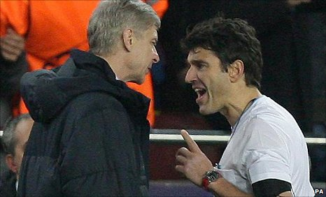 Arsenal manager Arsene Wenger (left) confronts referee Massimo Busacca after the defeat at Barcelona