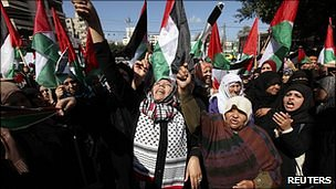 Palestinian women wave flags in protest