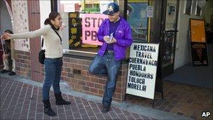 Ruby Acosta and Daniel Sandoval talk outside a travel shop in Santa Ana, California on 8 March 2011