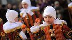 Children participate in the tradition of throwing oranges