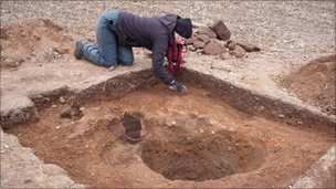 Archaeologists excavate the ground around the stone