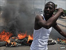 A man shouts next to burning tires on the streets of Abidjan