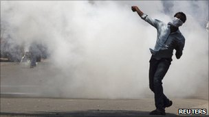 A pro-Telangana supporter throws a stone towards riot police firing tear gas during a demonstration in the southern Indian city of Hyderabad March 10, 2011.