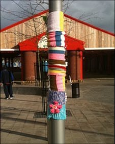 Seven short multi-coloured scarves on a lamp-post