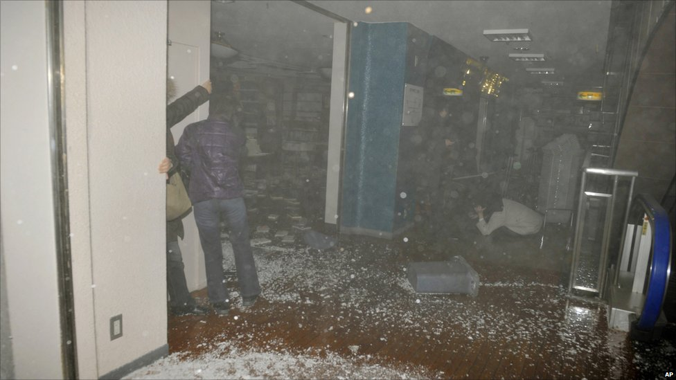 People react as the roof of a book store falls in in Sendai on 11 March 2011