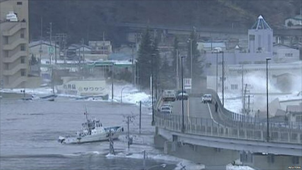 A boat is swept into a bridge by tsunami waters in Kamaishi city port on 11 March 2011