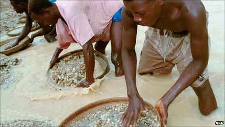 Workers pan for diamonds in a government-controlled diamond mine in Sierra Leone on 15 June 2001 near Kenema