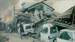 A man looks at a collapsed house in Kobe, Japan, after the 1995 quake