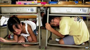File image of Japanese children taking shelter under their desks during an earthquake drill