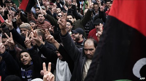 Libyan anti-government protesters shouts slogans while waving their country's former national flag during a protest in central Benghazi on 10 March