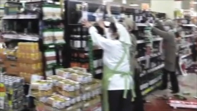 Supermarket worker holding on to shelves
