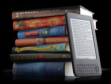 Amazon Kindle next to a pile of books
