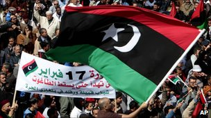 Anti-Libyan protesters wave the pre-Gadhafi Libyan flag