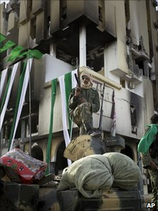 A pro-Gaddafi soldier stands on a tank next to a destroyed building in the main square of Zawiya, Libya, 11 March 2011