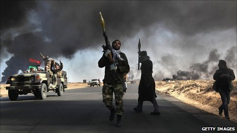 Libyan rebels battle government troops near Ras Lanuf as smoke from a damaged oil facility darkens the sky, 11 March 2011
