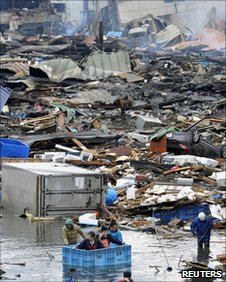 People use a floating container to escape floodwaters after a tsunami in Kesennuma, Japan, on 12 March, 2011.