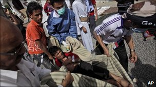 Injured protester taken away after clashes in Sanaa, 12 March 2011