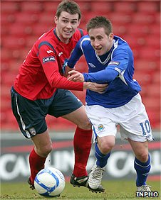 Stephen Lowry of Coleraine in action against Linfield's Michael Carvill
