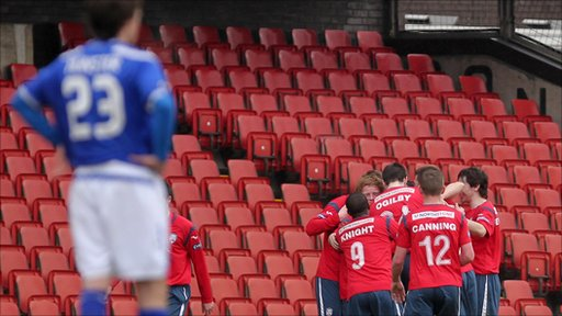 Linfield's Paul Munster watches as Coleraine players celebrate scoring at Windsor Park