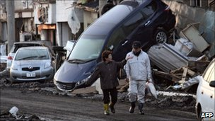 Couple walk past overturned vehicles in Miyako (12 March)