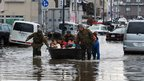 Soldiers pull a boat across floodwater as they help to evacuate residents of Tagajo city, Miyagi prefecture