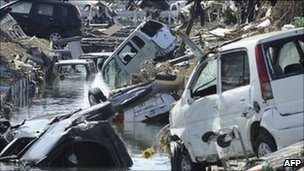 Vehicles swept into a canal by tsunami waves in Tagajo, Miyagi prefecture, 13 March