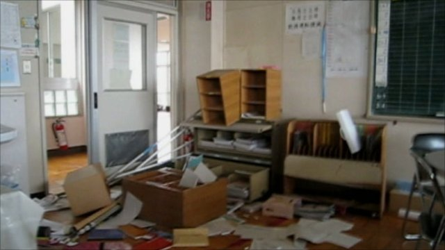 Shelves tipped over and paper on the floor of a staff room