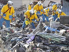 Searchers go through the rubble in Kamaishi, northern Japan