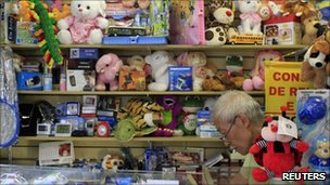 A vendor sits among mostly Chinese manufactured toys for sale in a shopping gallery known for selling cheap Asian products in Sao Paulo, 2 February 2011