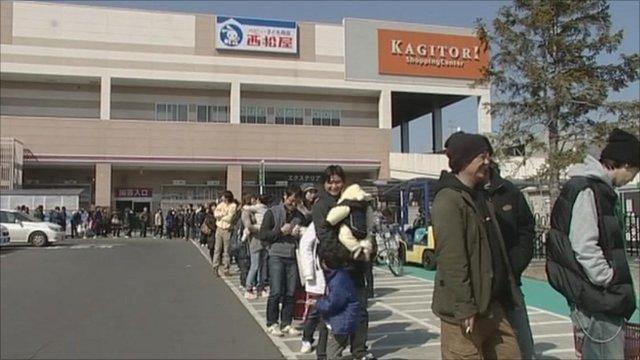 People wait in long queues for food in Sendai