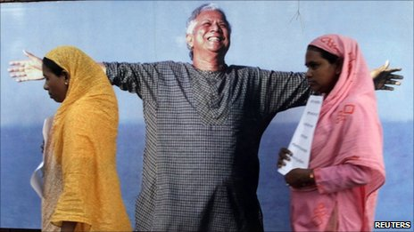 Grameen Bank employees walk in front of a portrait of Muhammad Yunus