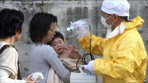 A one-year-old boy is checked for radiation exposure near the Fukushima plant