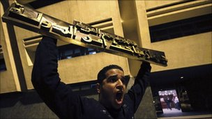 A protester holds up a sign from the State Security Investigation Service (SSIS) headquarters in Nasser City, Cairo
