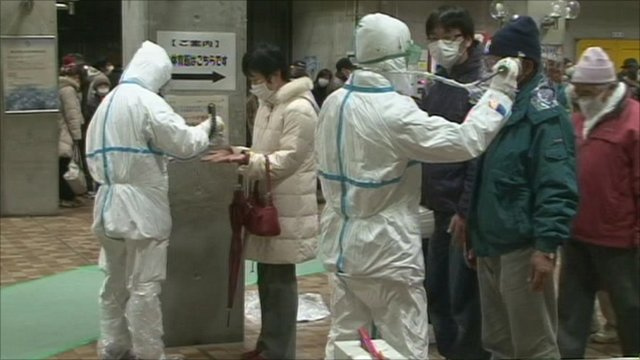 Men in protective suits checking residents