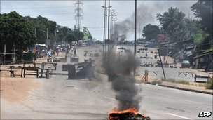 Residents walk past barricades and burning tires on the main road leading to the Abobo district of Abidjan on 15 March 2011