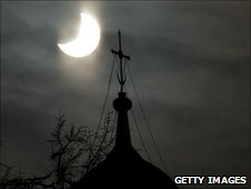A partial solar eclipse is seen above a cross of the Life-giving Trinity Russian Orthodox Cathedral in Moscow
