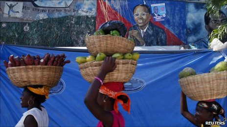 Women walk past a mural of former president Jean-Betrand Aristide in Port-au-Prince