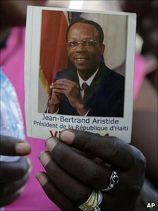 Woman holds photograph of Jean-Betrand Aristide on 11 March 2011
