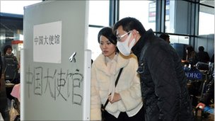 A couple check a Chinese Embassy noticeboard
