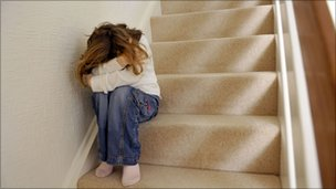 Young girl sits on staircase with arms across her face