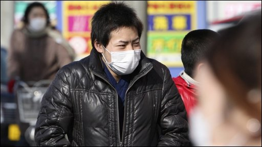 People wearing surgical masks walk down the streets of Okawara