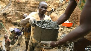 Miner passing a bucket in DRC