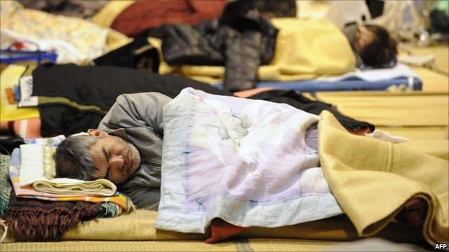 A man asleep on the floor of a relief centre