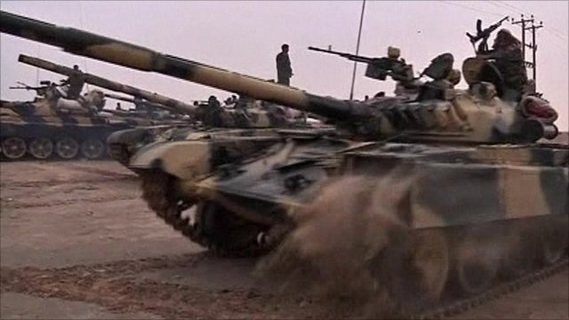 Pro Gaddafi tanks and fighters moving through the desert